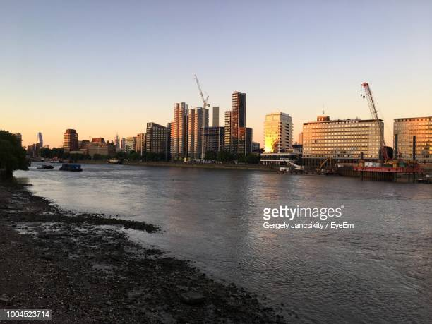 river and buildings against sky during sunset - greater london stock pictures, royalty-free photos & images