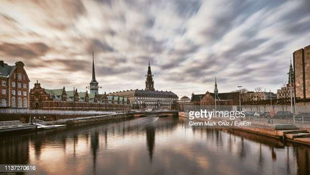 river and buildings in city against cloudy sky - copenhagen stock pictures, royalty-free photos & images