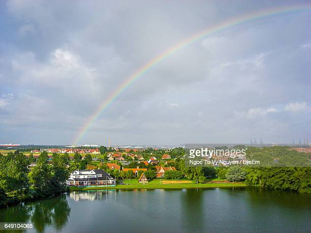 river and houses with trees against cloudy sky during rainy season - rainy season stock pictures, royalty-free photos & images