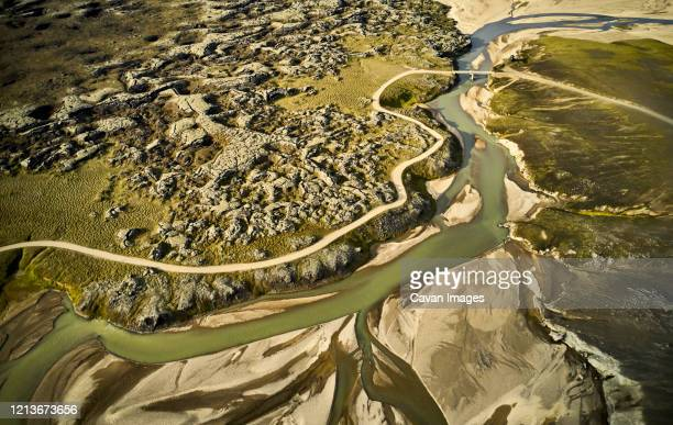 river and road in rough highlands - drainage_basin stock pictures, royalty-free photos & images