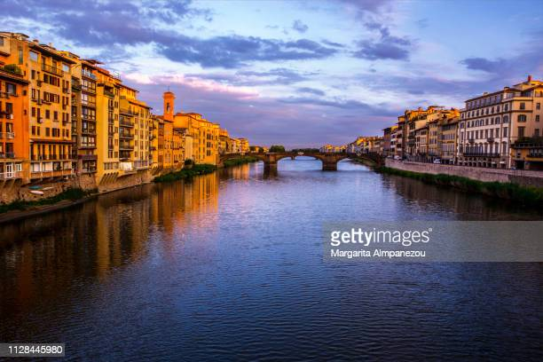 River Arno and Florence during dawn with a dramatic sky reflected in the water