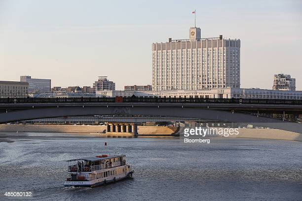 A river boat passes beneath a bridge on the Moskva River near the Russian White House government building center in Moscow Russia on Sunday Aug 23...