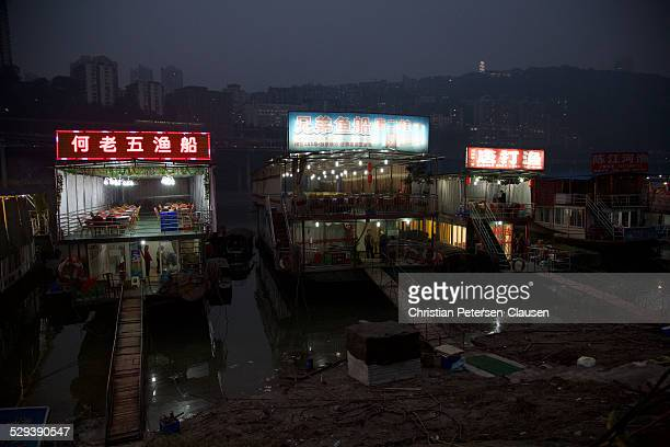 River boats serving as fish restaurants lie permanently moored to the heavily polluted banks of the Jialing River in the Huaxinjie neighborhood in...