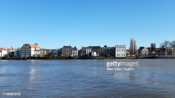 river by buildings against clear blue sky - dordrecht stock pictures, royalty-free photos & images