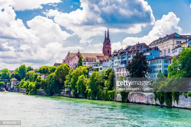 river by buildings against cloudy sky - basel switzerland stock pictures, royalty-free photos & images