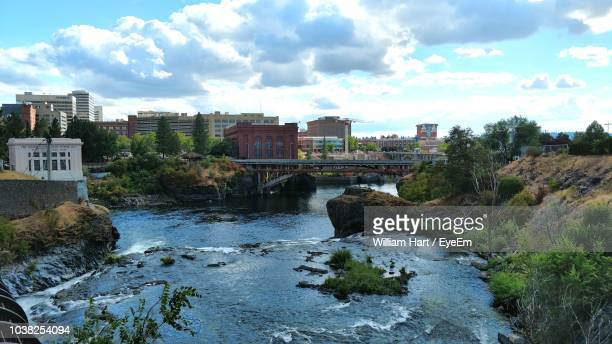 river by buildings against sky - spokane stock pictures, royalty-free photos & images