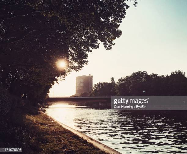 river by city against clear sky during sunset - oberhausen stock-fotos und bilder