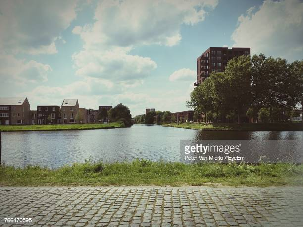 river by city against sky - tilburg stock pictures, royalty-free photos & images