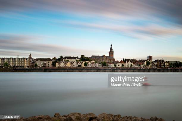 river by city against sky - nijmegen stock pictures, royalty-free photos & images