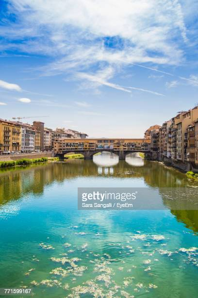 river by cityscape against blue sky - ponte vecchio stock photos and pictures