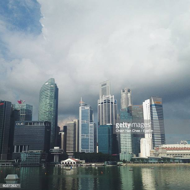 River By Cityscape Against Cloudy Sky