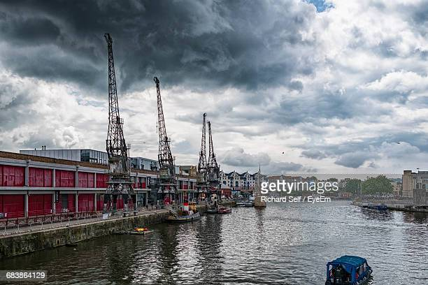 River By Cranes And Buildings Against Cloudy Sky