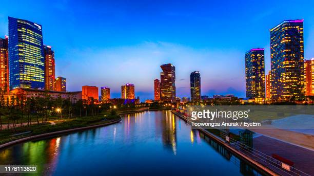 river by illuminated buildings against sky at dusk - songdo ibd stock pictures, royalty-free photos & images