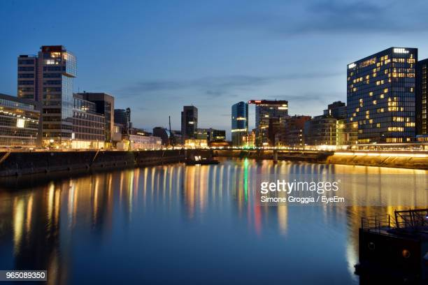 River By Illuminated City Against Sky At Dusk