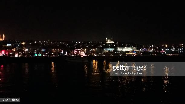 river by illuminated city against sky at night - hilal stock photos and pictures