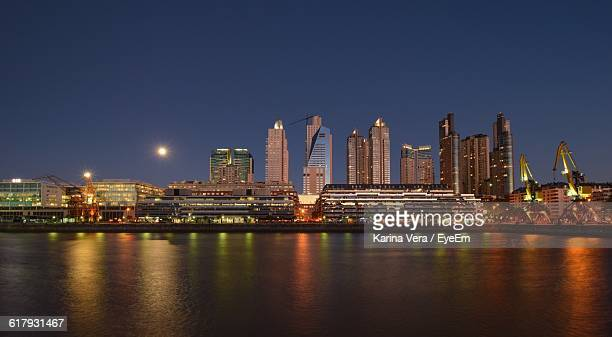 River By Illuminated Cityscape Against Sky At Dusk