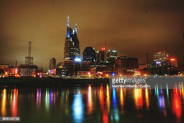 River By Illuminated Cityscape Against Sky At Night