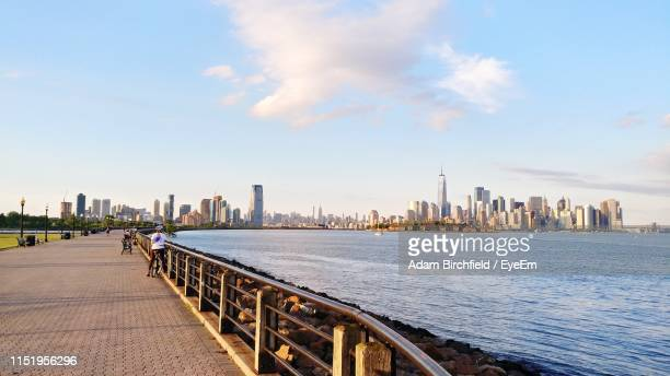 river by modern buildings against sky in city during sunset - jersey city stockfoto's en -beelden