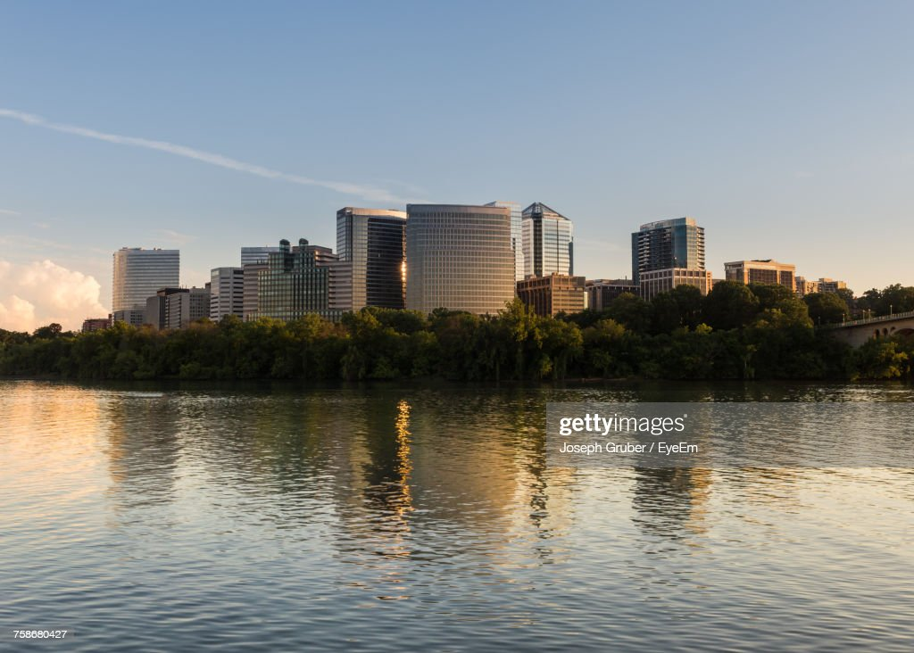 River By Modern Buildings Against Sky In City : Stock Photo