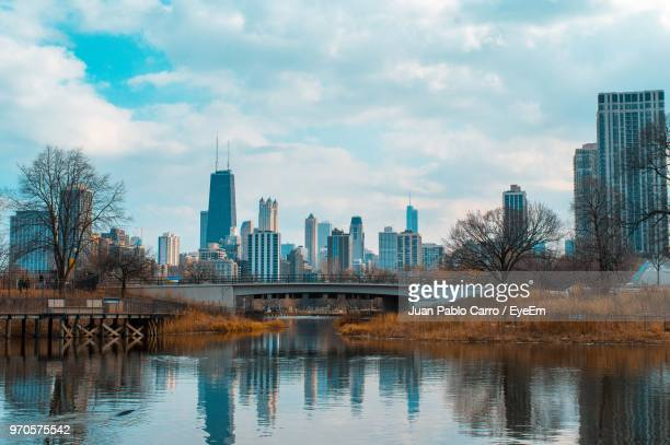 river by modern buildings against sky in city - waterfront stock pictures, royalty-free photos & images