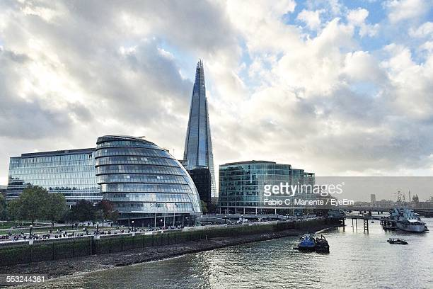 River By Shard London Bridge Amidst Buildings Against Cloudy Sky In City