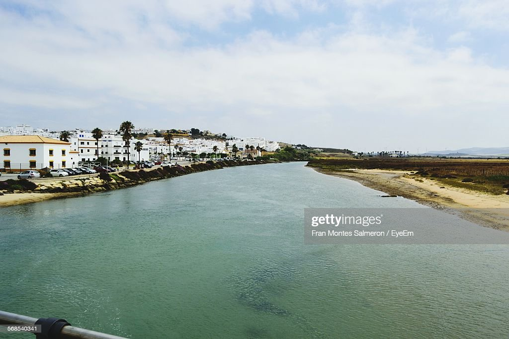 River By Town Against Cloudy Sky : Stock Photo