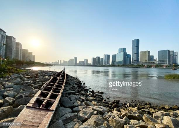 river channel, stranded boat and city skyline - fuzhou stock pictures, royalty-free photos & images