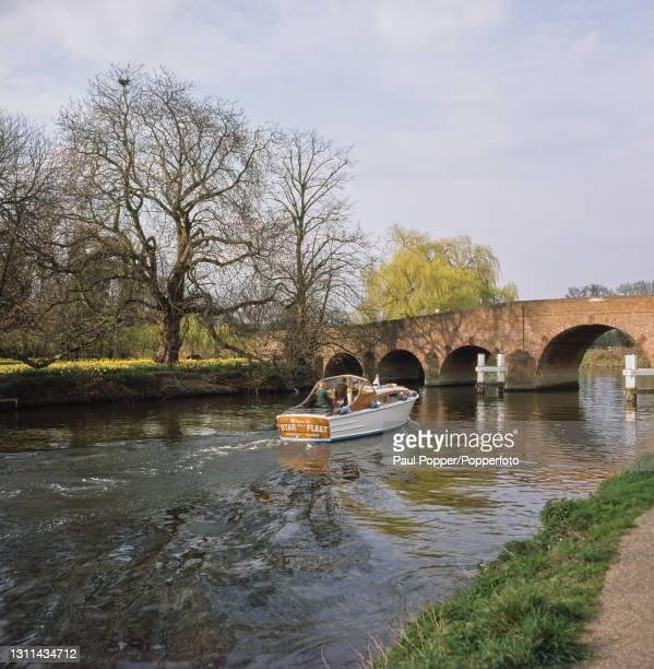 River cruiser boat moves upstream under Sonning Bridge, a road bridge over the River Thames between the village of Sonning in Berkshire and Sonning...