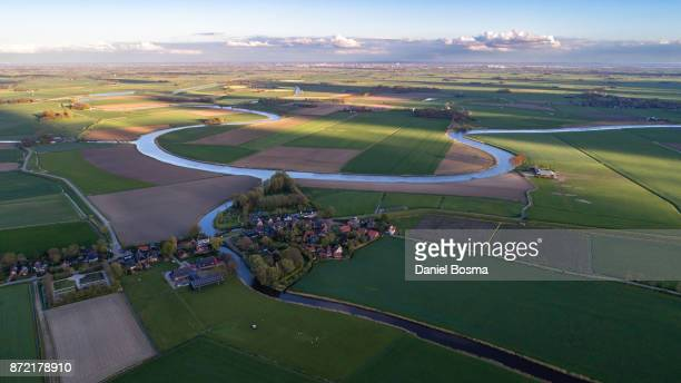 A river curving it's way through a cultivated Dutch landscape, seen from the air