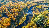 River Dam among Bright Autumn Forest. Bird's-eye View