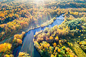 River Dam among Trees. Bird's-eye View with Colorful Sunbeams