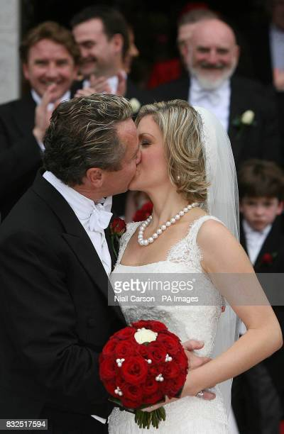 River Dance star Michael Flatley kisses his wife Niamh O'Brien as the couple leave St Patrick's church in Fermoy Co Cork after their wedding today