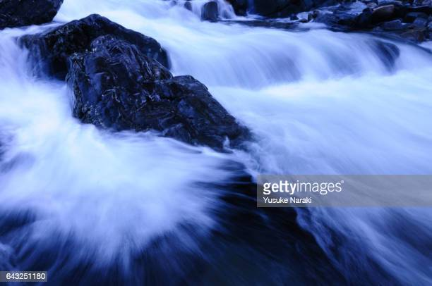 River flow and a black luster rock splitting the water