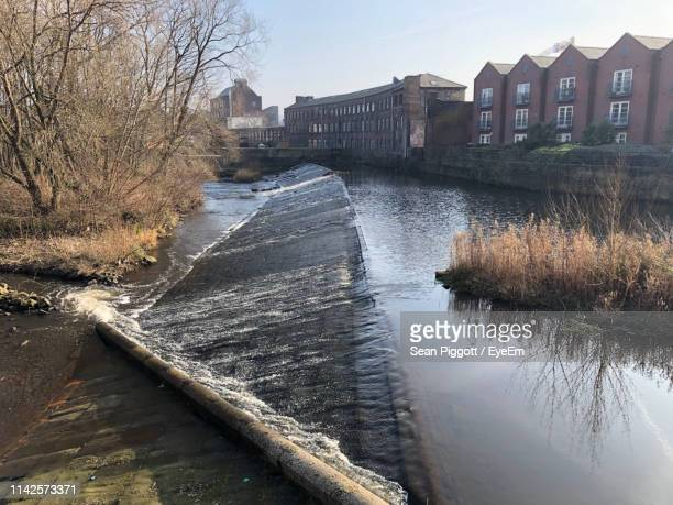 river flowing amidst buildings against sky - sheffield stock pictures, royalty-free photos & images