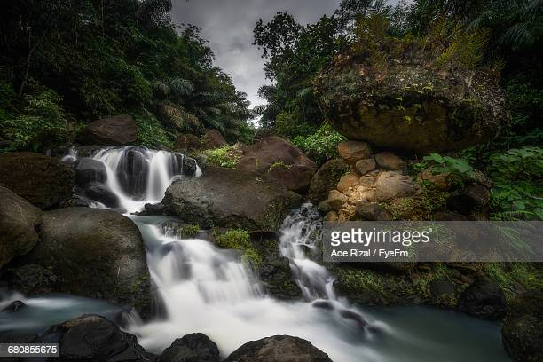 river flowing through rocks - ade rizal stock photos and pictures