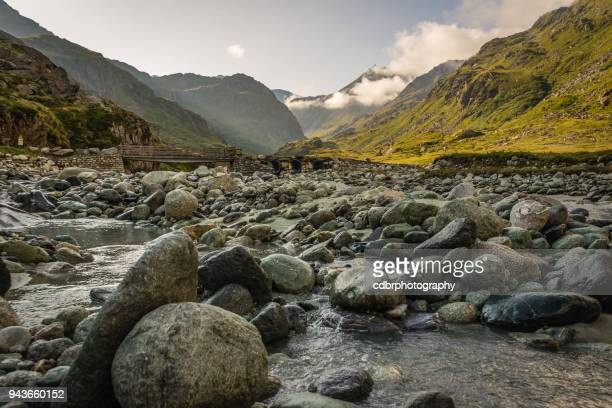 river flowing through the swiss alps, sunrise - rock stock pictures, royalty-free photos & images