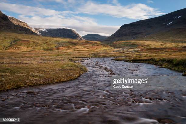 river flows through the scenic syterskalet mountain valley near viterskals hut, kungsleden trail, lapland, sweden - swedish lapland stock-fotos und bilder