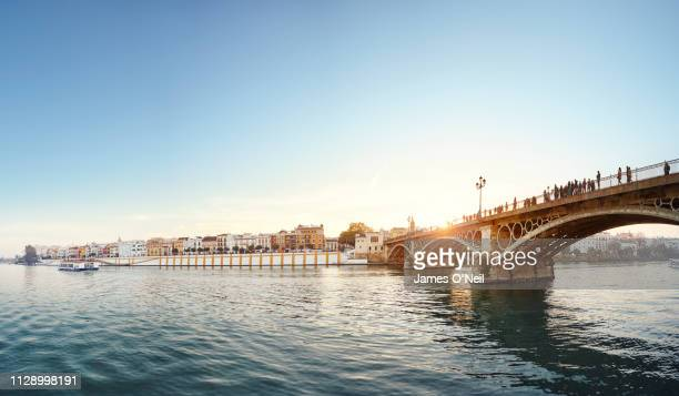 river guadalquivir and the isabel ii bridge at sunset, seville, spain - seville stock pictures, royalty-free photos & images