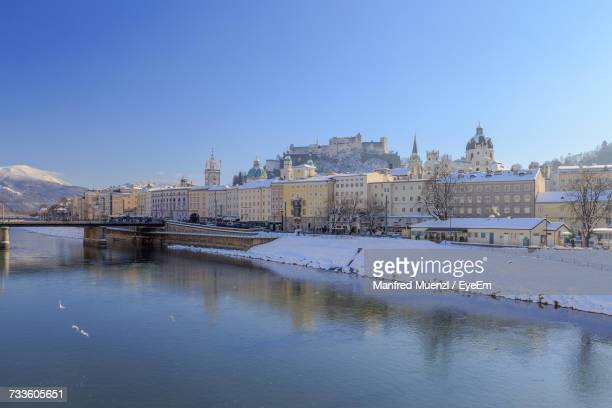 River In City Against Clear Blue Sky During Winter