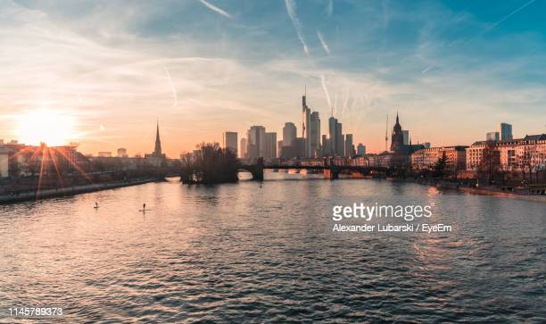 river in city against sky during sunset - frankfurt am main stock-fotos und bilder