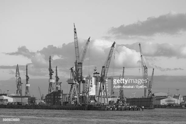 River In Front Of Cranes At City Against Cloudy Sky