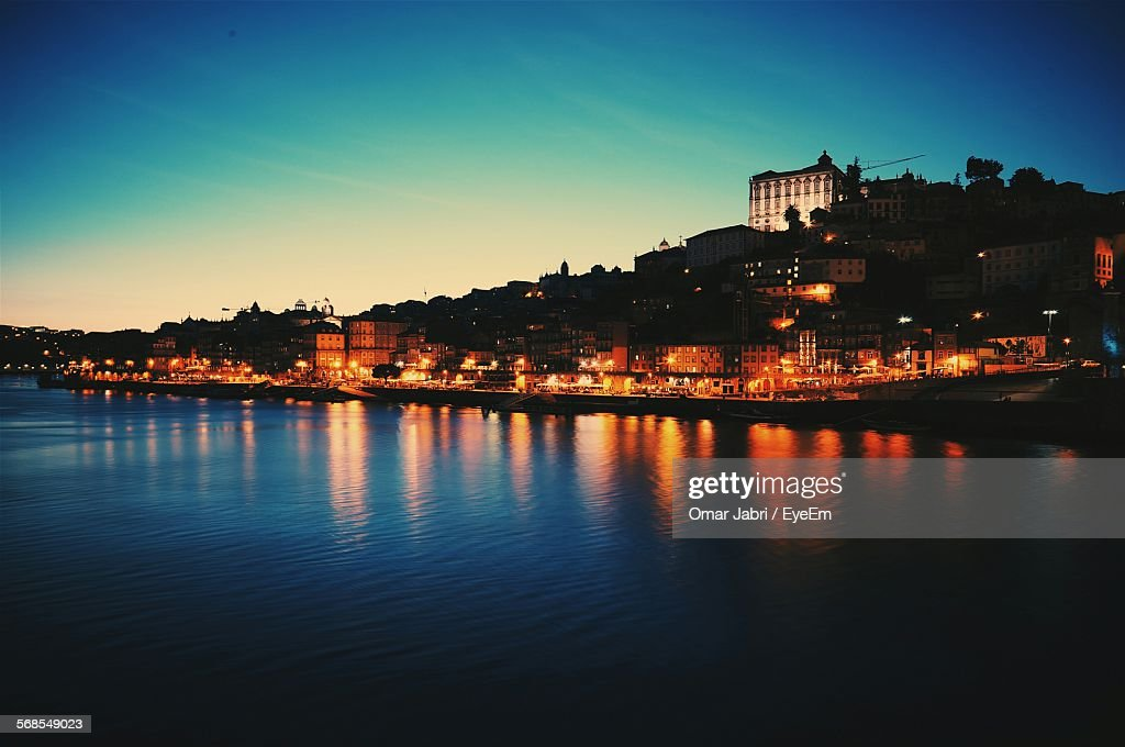 River In Front Of Illuminated Cityscape Against Blue Sky At Dusk : Stock Photo