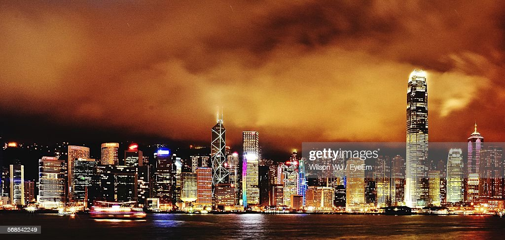River In Front Of Illuminated Cityscape Against Cloudy Sky At Dusk : Stock Photo