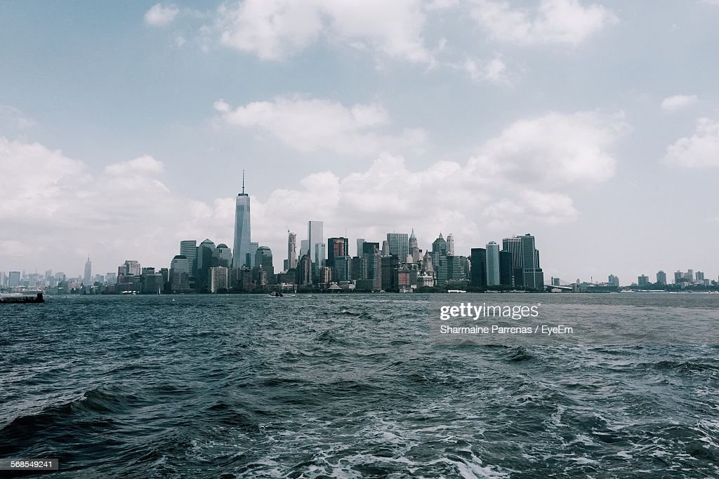 River In Front Of One World Trade Center Amidst Buildings Against Cloudy Sky : Stock Photo