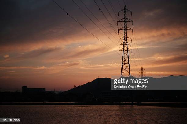river in front of silhouette electricity pylon against cloudy sky during sunset - syoichiro oka stock-fotos und bilder