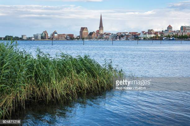 river in front of town against sky - rostock stock pictures, royalty-free photos & images