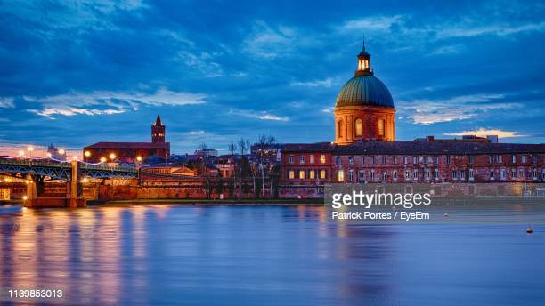 river in illuminated city against cloudy sky at dusk - toulouse - fotografias e filmes do acervo