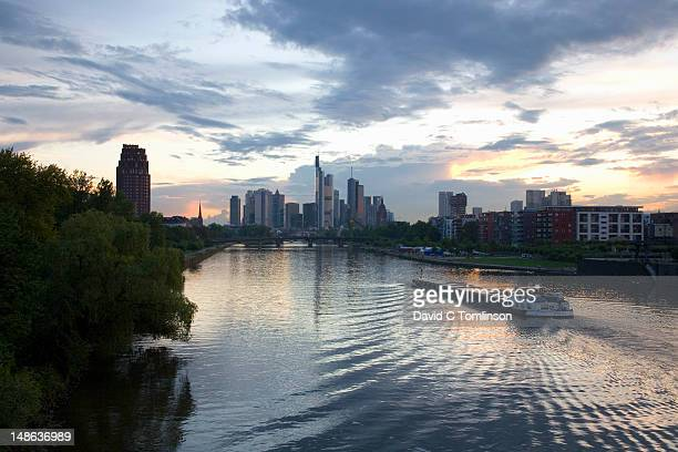 River Main and Frankfurt's high-rise business district, famously known as Mainhattan, at sunset with river barge in foreground.