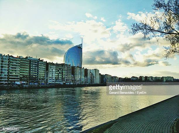 river meuse flowing by buildings against sky - liege stock pictures, royalty-free photos & images