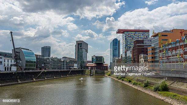 River Next To Buildings In City Against Cloudy Sky